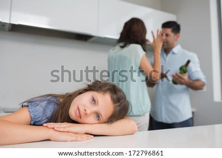 Close-up portrait of a sad girl while parents quarreling in the kitchen - stock photo