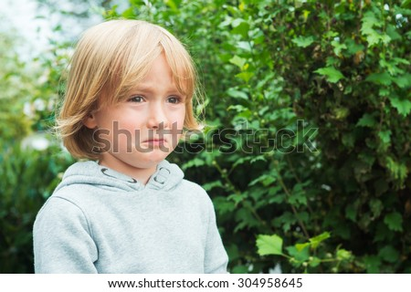 Close up portrait of a sad little boy - stock photo
