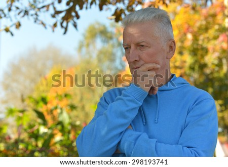 Close-up portrait of a sad  man in park - stock photo