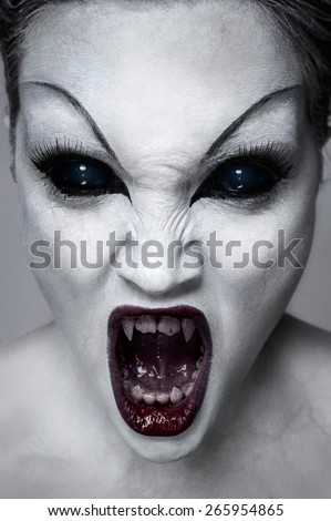 Close up portrait of a screaming undead girl with sharp teeth, white skin and black eyes - stock photo