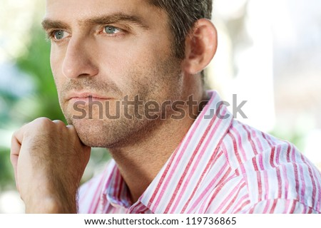 Close up portrait of a senior businessman resting his chin on his hand in the city. - stock photo