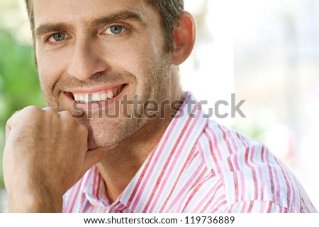 Close up portrait of a senior businessman resting his chin on his hand in the city, smiling. - stock photo