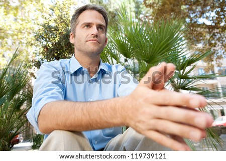 Close up portrait of a senior businessman sitting in a city park and holding his hands together, being thoughtful, outdoors. - stock photo