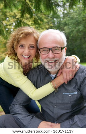 Close up portrait of a senior couple laughing together outdoors - stock photo