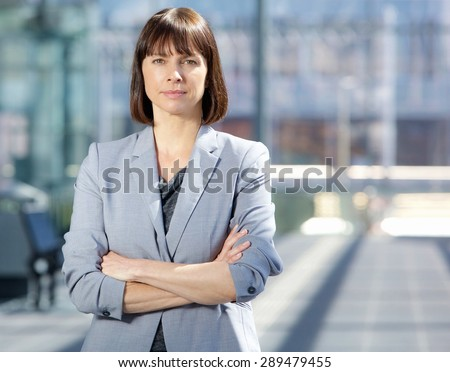 Close up portrait of a serious business woman in gray suit standing in the city - stock photo