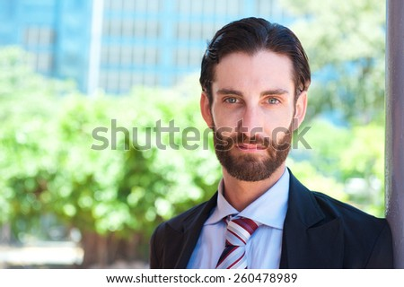 Close up portrait of a serious businessman standing outside - stock photo