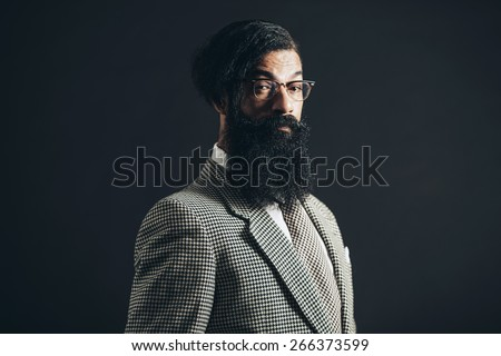Close up Portrait of a Serious Man with Long Beard, Wearing Checkered Formal Attire, Staring at Camera on a Black Background. - stock photo