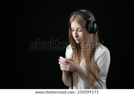 Close up portrait of a serious teenager girl in wired headphones listening music from personal phone - stock photo