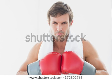 Close-up portrait of a serious young man in red boxing gloves over white background - stock photo