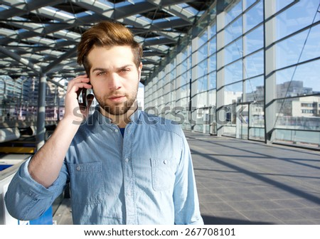 Close up portrait of a serious young man talking on mobile phone inside building - stock photo