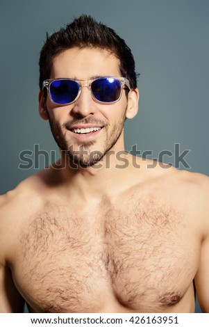Close-up portrait of a sexy young man in sunglasses. Studio shot. - stock photo