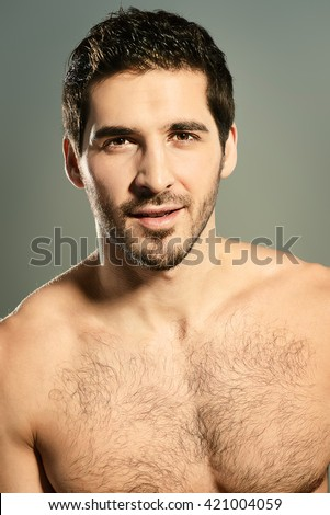 Close-up portrait of a sexy young man with perfect muscular body slightly smiling invitingly at camera. Gray background. Studio shot. - stock photo