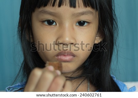 close up portrait of a sick girl eat cookie lying in a hospital bed - stock photo