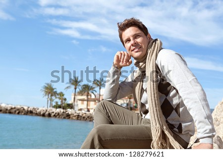 Close up portrait of a smart man relaxing on a beach during the winter with a blue sky and sea in the background, smiling. - stock photo