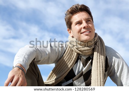 Close up portrait of a smart man smiling and relaxing against a bright blue sky on a sunny winter day. - stock photo