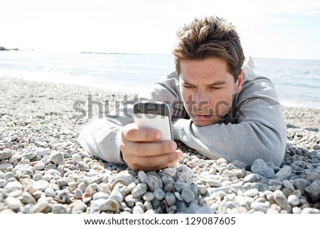 "Close up portrait of a smart man using a ""smart phone"" while laying down on a white pebble beach during a sunny day. - stock photo"