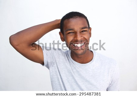 Close up portrait of a smiling african american guy with hand in hair - stock photo