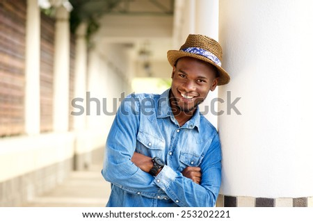 Close up portrait of a smiling african american man relaxing with arms crossed - stock photo