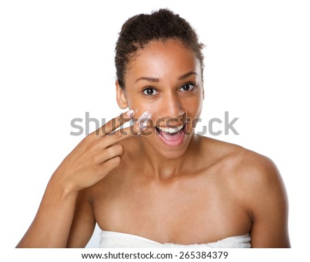 Close up portrait of a smiling african american woman applying lotion on skin - stock photo
