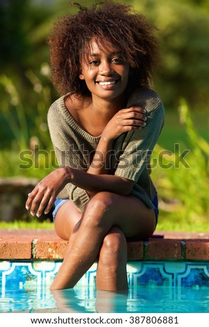 Close up portrait of a smiling african american woman sitting by pool with feet in water - stock photo