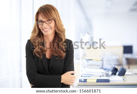 Close-up portrait of a smiling attractive mature business woman with arms crossed standing in her office - stock photo