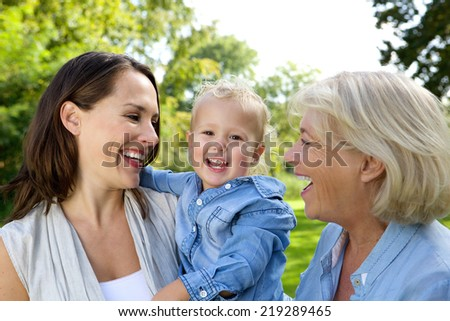 Close up portrait of a smiling baby with mother and grandmother - stock photo