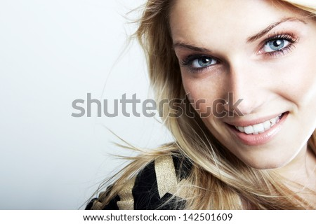 Close-up portrait of a smiling beautiful blonde caucasian woman with blue eyes, looking at camera, on a gray background with copy-space - stock photo