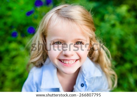 Close-up portrait of a smiling blond little girl wearing a blue jacket in sunny summer day - stock photo