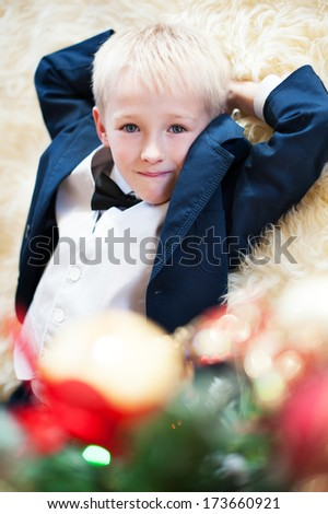 close up portrait of a smiling boy in a suit with a bow tie who lay on the floor and dreams about New Year - stock photo