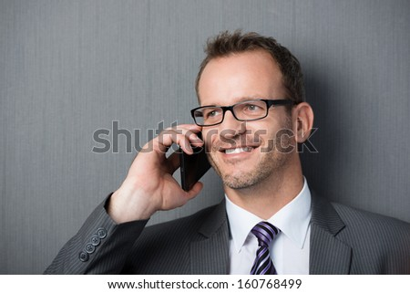 Close-up portrait of a smiling business man using the mobile phone - stock photo