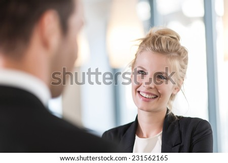 close-up portrait of a smiling businesswoman talking with a man - stock photo