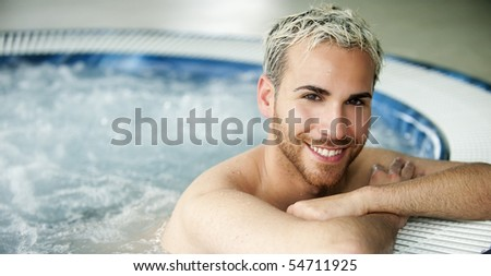 Close up portrait of a smiling handsome man in jacuzzi - stock photo