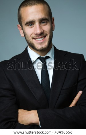 Close-up portrait of a smiling handsome young business man - stock photo