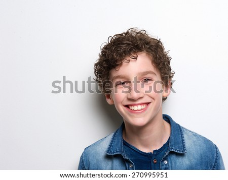 Close up portrait of a smiling little boy with curly hair on white background - stock photo