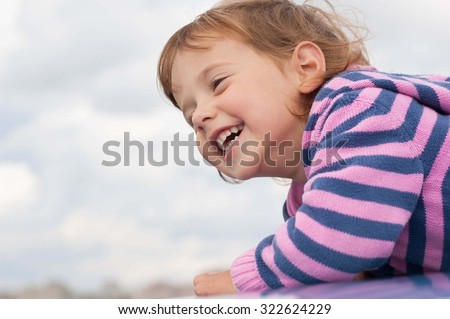 close-up portrait of a smiling little girl profile on a background of cloudy sky - stock photo
