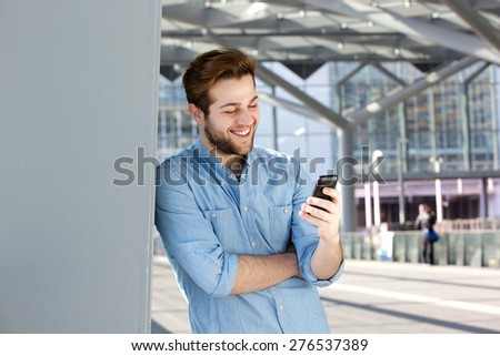 Close up portrait of a smiling man reading text message on mobile phone - stock photo