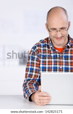 Close-up portrait of a smiling mature balding caucasian man, wearing glasses, and sitting at the office desk looking at a laptop screen - stock photo