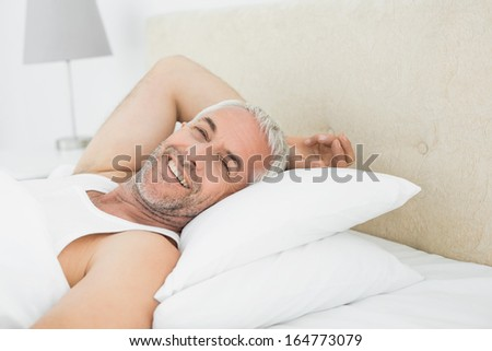 Close-up portrait of a smiling mature man resting in bed at home