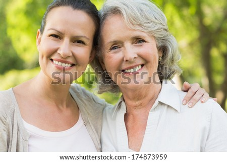 Close-up portrait of a smiling mature woman with adult daughter at the park