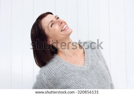 Close up portrait of a smiling middle aged woman looking up - stock photo