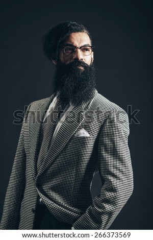 Close up Portrait of a Smiling Thoughtful Man with Long Goatee Beard, Wearing Checkered Formal Wear While Looking to the Right of the Frame on a Black Background. - stock photo