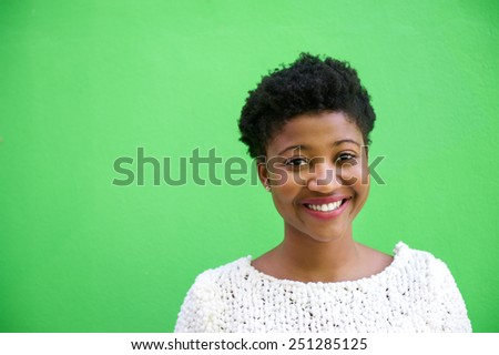 Close up portrait of a smiling young african american woman isolated on green background - stock photo