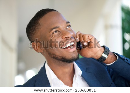 Close up portrait of a smiling young businessman calling by mobile phone - stock photo
