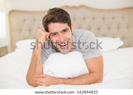 Close up portrait of a smiling young man resting in bed at home