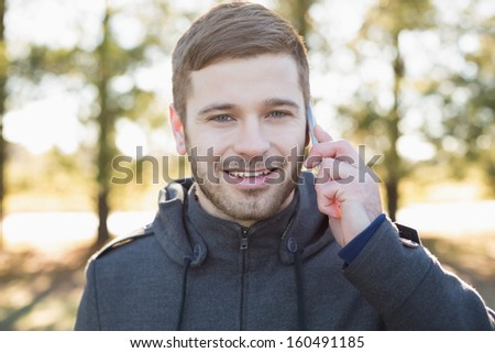 Close-up portrait of a smiling young man using mobile phone in the forest