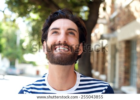 Close up portrait of a smiling young man with beard looking up