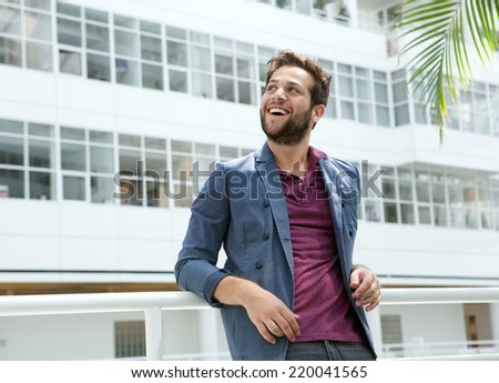 Close up portrait of a smiling young man with beard standing in white building - stock photo