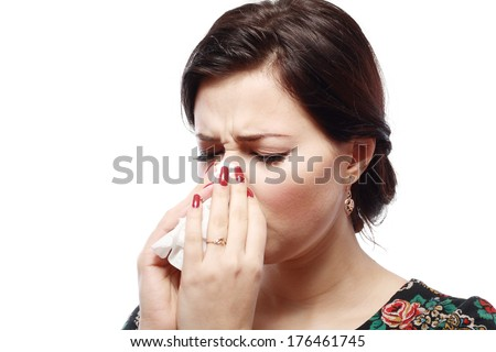 Close-up portrait of a sneezing woman with allergy or cold  - stock photo