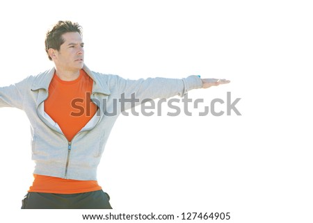 Close up portrait of a sports man stretching his arms to the sides while standing against a sunny sky. - stock photo