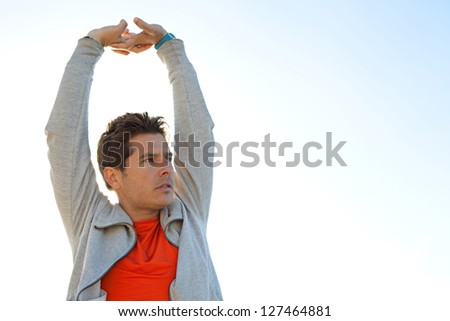 Close up portrait of a sports man stretching his arms up in the air against a sunny blue sky with sun rays filtering through his neck. - stock photo